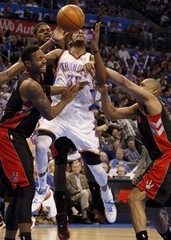 Oklahoma City Thunder's small forward Durant is fouled by Toronto Raptors' center Magloire during their NBA basketball game in Oklahoma City