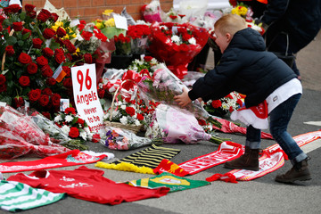 A boy leaves a tribute for the 96 victims of the Hillsborough disaster are seen at Anfield in Liverpool