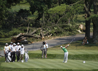 Hunter Mahan of the U.S. hits off the second tee with a downed tree in the background during the third round of the AT&T National golf tournament in Bethesda