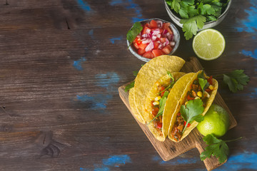 Traditional Mexican tacos with tomatoes, meat, herbs. Dark background. Fast food.