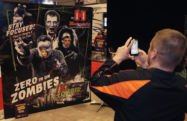 Two young attendees get there picture taken with a zombie poster during the NRA 141st Annual Meetings & Exhibits in St. Louis