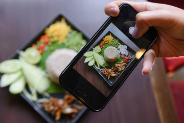 Women user smart phone to take picture of Rice mixed with shrimp paste (Kao Cluk Ka Pi)