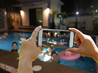 Take a group picture of blurred people on swimming pool background with hand holding smartphone in the fun partty on night