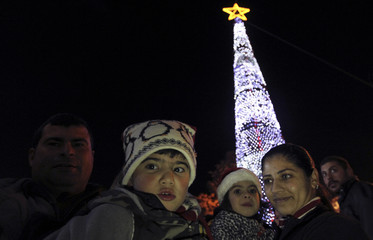 A family poses during the lighting event of a 27-metre (88 ft) tall Christmas tree, part of the celebrations of the Christian communities in Madaba city