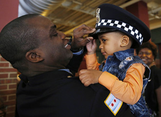 Chicago Police officer Darien Givens puts his hat on his son Jeremiah after graduating with the newest class of police recruits at their graduation ceremony in Chicago