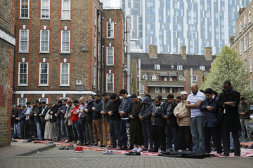 Muslims attend Friday prayers in the courtyard of a housing estate next to the small BBC community centre and mosque in east London