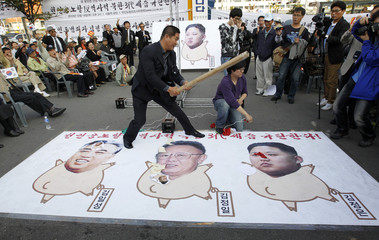 An anti-North Korea protester hits illustrations of Kim Il-sung, Kim Jong-il, and Kim Jong-un during a rally denouncing the three generations of North Korean leaders from the Kim family in Seoul