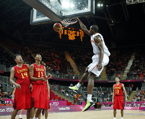 Spain's Ibaka dunks as China's Wang and team mate Yi look on during their men's Group B basketball match at the London 2012 Olympic Games in the Basketball arena