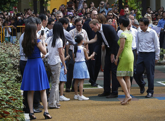 Britain's Prince William and Catherine, Duchess of Cambridge, greet residents during a tour at Queenstown public housing estate in Singapore