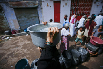 A woman carries a bucket filled with drinking water after collecting it from a local government supply truck in Ahmedabad