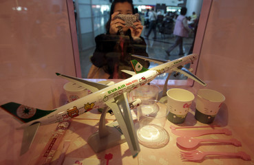 A passenger takes pictures of Eva Airlines' Hello Kitty-themed products displayed in Taoyuan International Airport, northern Taiwan