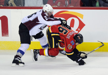 Colorado Avalanche's Paul Stastny knocks Calgary Flames' Tom Kostopoulos to the ice during their NHL game in Calgary