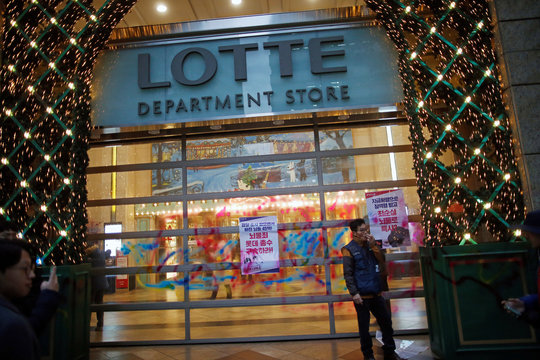 A member of Korean Confederation of Trade Unions smokes a cigarette in front of the defaced entrance of Lotte department store during a general strike calling for South Korean President Park Geun-hye to step down, in central Seoul