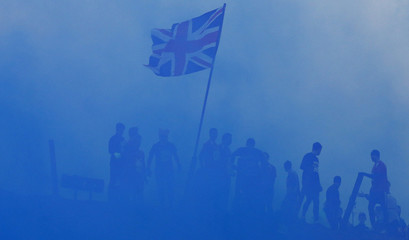 Competitors pass a Union flag as they run through clouds of blue smoke during the Tough Guy event in Perton