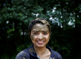 A student of Himalayan Agriculture College with mud on her face poses for a picture while celebrating Asar Pandra festival in Lalitpur