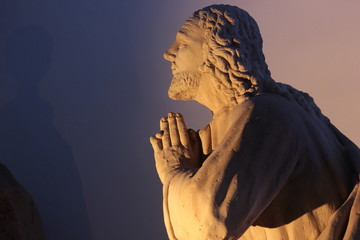 Praying statue in spiritual illumination