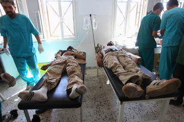 Anti-Gaddafi fighters injured amidst heavy shelling on a roundabout in Sirte, receive medical treatment at a field hospital, 20 km (12 miles) east of Sirte