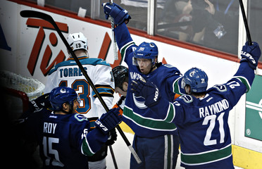 Vancouver Canucks Hansen celebrates his goal against the San Jose Sharks with teammates Raymond and Roy  during their NHL Western Conference quarter final hockey playoff in Vancouver