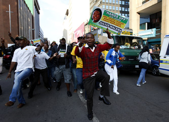 Supporters of ANCYL President Malema hold placards during his appearance at the Johannesburg court
