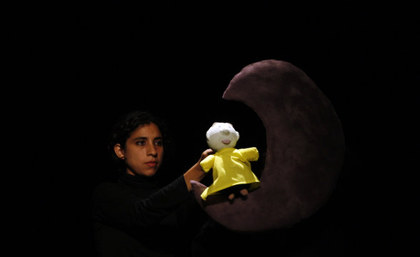 An artist performs with a puppet and a moon during the International Festival of Marionettes in Lima