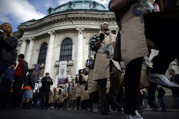 Protesting students wearing fake military uniforms march during a demonstration in front of Sofia University