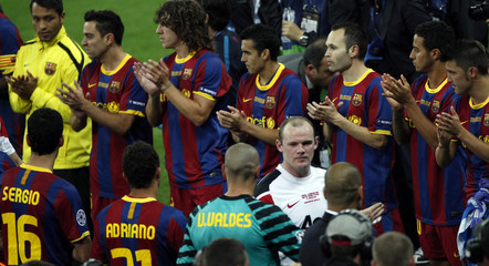 Barcelona's players applaud as Manchester United's Wayne Rooney walk by after their Champions League final soccer match at Wembley Stadium in London
