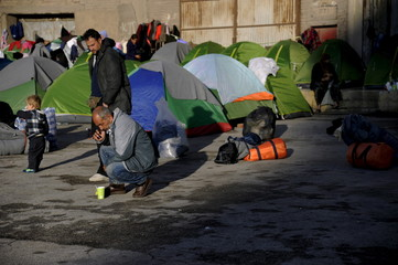 Refugees and migrants are seen by their tents, next to an old building at the port of Piraeus, near Athens