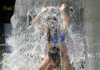 A girl plays in the waterfall at the the fun bath in Endenich