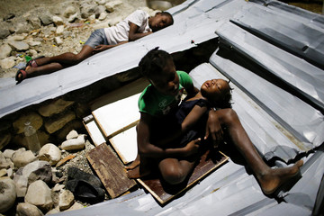 Children sleep over metal sheets in a partially destroyed school used as a shelter after Hurricane Matthew hit Jeremie