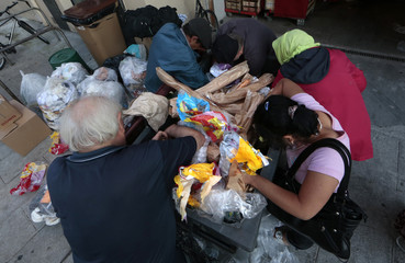 Eugene, an 87-year-old retired Frenchman, searches for food in a garbage container with a group of Romanian people next to a supermarket in Nice