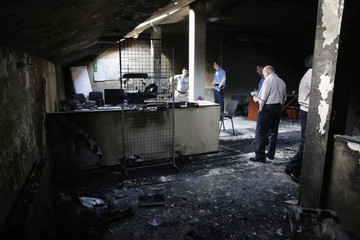"""Interior Ministry security force members and investigators work inside a burnt regional office of the All-Ukrainian Union """"Svoboda"""" Party, led by Oleh Tyahnybok, in Odessa"""
