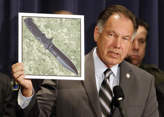 Rackauckas holds up picture of a knife similar to the one he accuses of being used by Ocampo at a news conference at the district attorney's office in Santa Ana