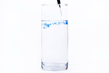 Blue paint falls in a glass with water