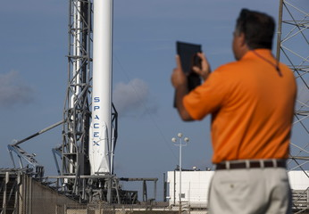 A NASA media escort takes a photo of the unmanned SpaceX Falcon 9 rocket with Dragon capsule as it sits on launch pad 40 at the Cape Canaveral Air Force Station in Cape Canaveral, Florida