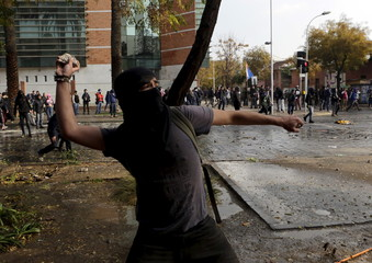 A student throws stones as they clash with riot police during a demonstration to demand changes in the education system, in Santiago