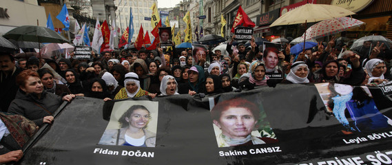 Pro-Kurdish demonstrators shout slogans as they march holding a banner with pictures of the three slain Kurdish activists during a protest in central Istanbul