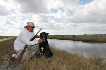 Permit holding hunter Irwin and his dog pose for a picture on a canal bank in the Everglades while in search of Burmese pythons during a state-sponsored snake hunt, near Homestead