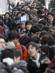 People stand in a line to purchase Apple's new iPad in front of Apple Store Ginza in Tokyo