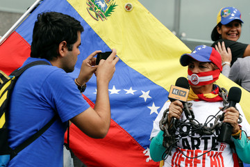 A man takes a picture of a woman as she wears a gag and a chain, and holds microphones during a rally to commemorate World Press Freedom Day in Caracas