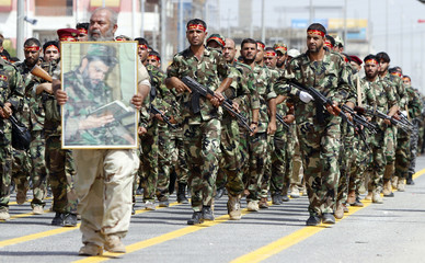 Mehdi Army fighters loyal to Shi'ite cleric Moqtada al-Sadr march during a parade in Basra