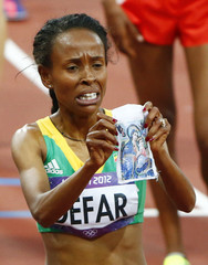 Ethiopia's Meseret Defar holds a piece of cloth with an image of a religious icon after she won the women's 5000m final during the London 2012 Olympic Games