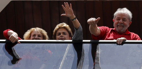 Former Brazilian President Lula, his wife Marisa and Brazilian President Rousseff wave from the window of his home in Sao Bernardo do Campo