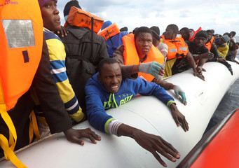 Migrants try to reach a rescue craft from their overcrowded raft, as lifeguards from the Spanish NGO Proactiva Open Arms rescue all 112 on aboard