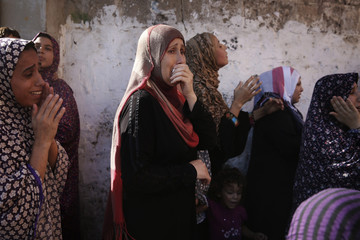 Women grieve during the funeral of the four Palestinian children from the Baker family, whom medics said were killed by a shell fired by an Israeli naval gunboat, in Gaza City