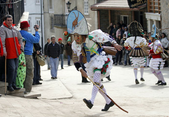 "A carnival reveller dressed as a ""Peliqueiro"" runs through a street in Spain's northwestern village of Laza"