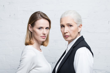 Portrait of serious women standing together and looking at camera, young and senior people