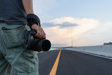 Man holding a camera standing on the street.A traveler or photographer taking pictures on the road trip.