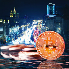 Photo Golden Bitcoins (new virtual money )close-up on a blue background.Coins  against the background of the night city. Conceptual photo.