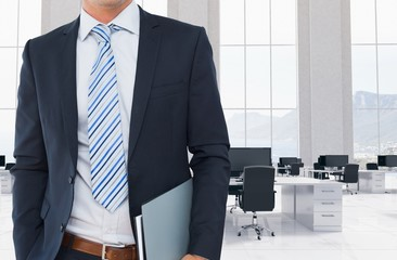 Businessman is holding note book against office background