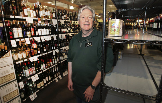 Wine clerk David Hedstrom stands next to partially empty shelves at Central Market in Shoreline